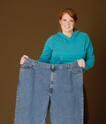 woman holding up large pants after weight loss links to weight loss surgery