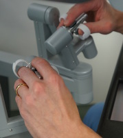 close-up of Dr. Bell's hands operating the da Vinci surgical system.